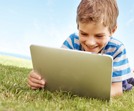 boy reading outside on tablet