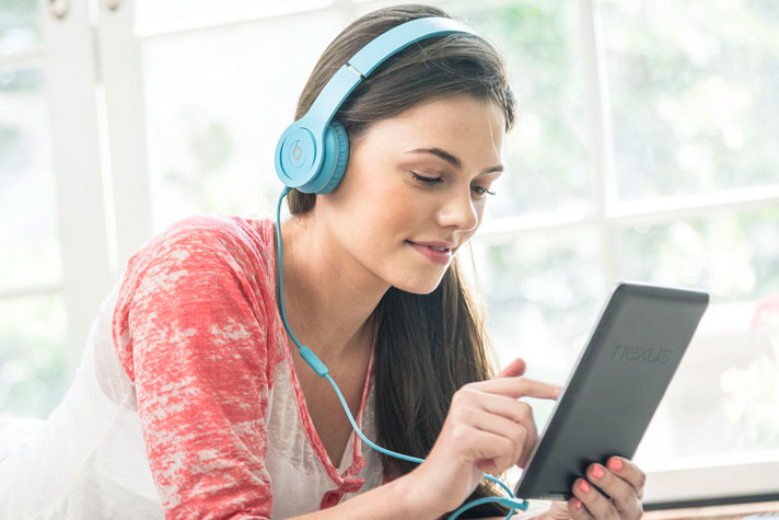 a student listening to audiobooks on her tablet