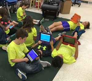 students reading with devices in classroom