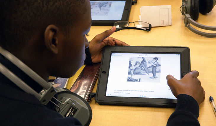 Student reading Learning Ally audiobook on tablet