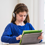 photo of young female student enjoying audiobooks on their tablet